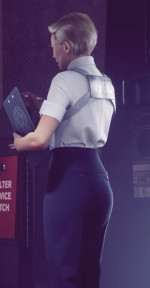 An image from quarter-rear perspective of a blonde, short-haired woman dressed in office attire standing with clipboard
