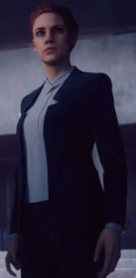 An image in quarter-front perspective of a standing red-haired woman wearing a pants-suit