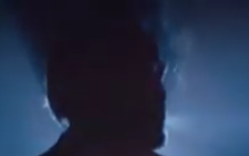 Shadowy silhouette of a man's head turned in profile as he exhales cigarette smoke on a blurry blue background